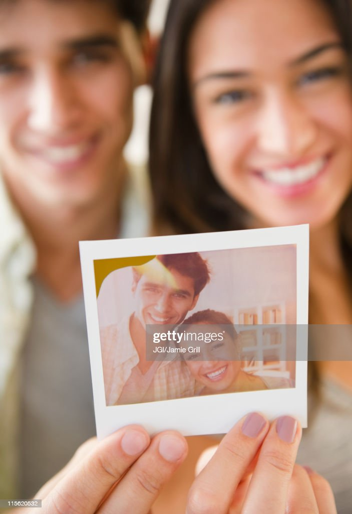 Couple holding photograph of themselves : Stock Photo