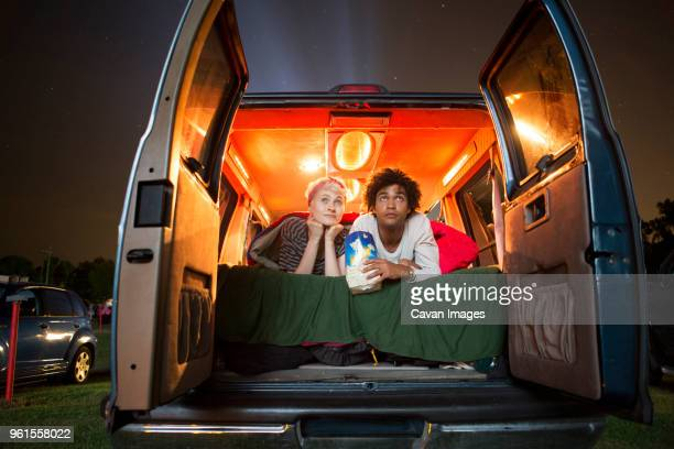 couple holding popcorn while sitting in camping van during drive-in movie - drive in movie stock pictures, royalty-free photos & images