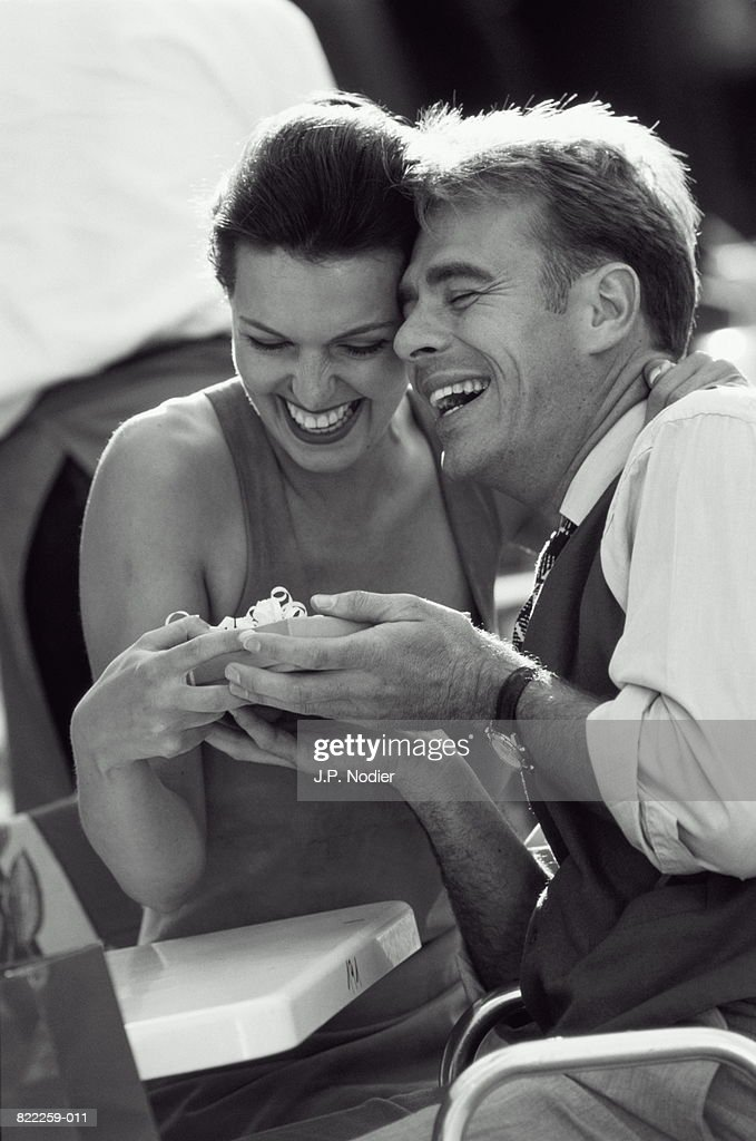 Couple holding present, laughing, sitting in outdoor cafe (B&W) : Stock Photo