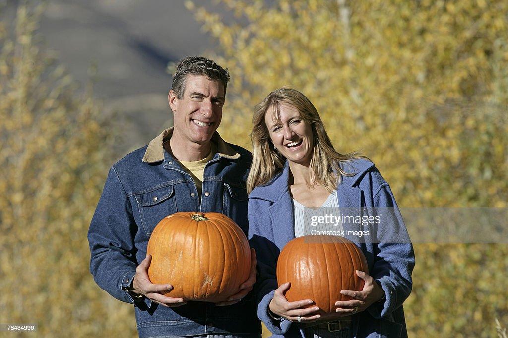 Couple holding pumpkins : Stockfoto