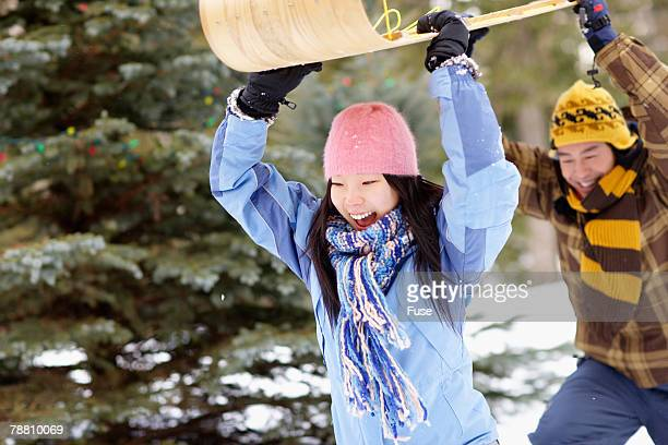 couple holding sled - tobogganing stock pictures, royalty-free photos & images