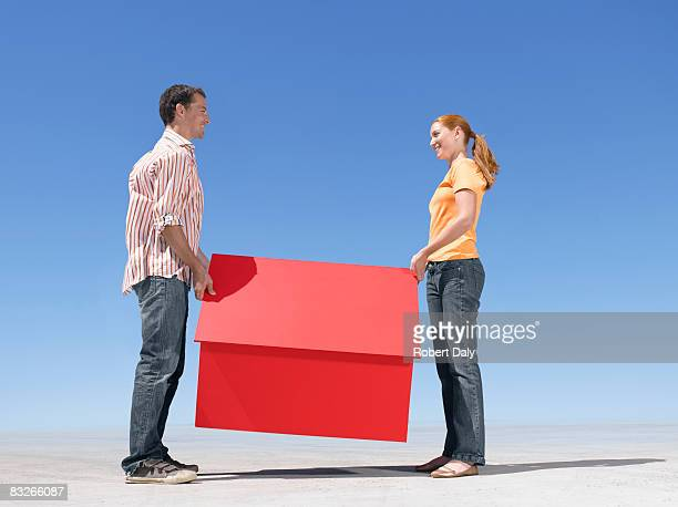 couple holding small model house - bridging the gap stock pictures, royalty-free photos & images