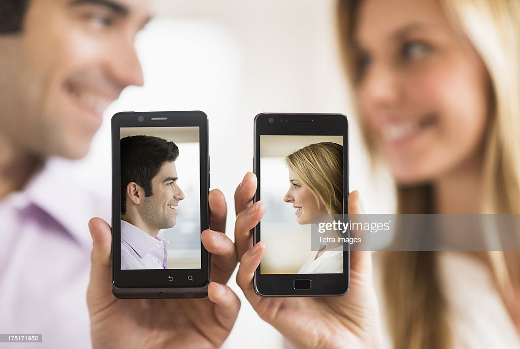 Couple holding smartphones with their pictures on : Stock Photo