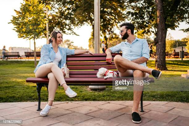 couple holding social distance on bench - park bench stock pictures, royalty-free photos & images