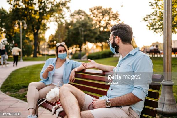 couple holding social distance on bench - romance stock pictures, royalty-free photos & images