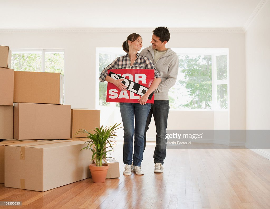 Couple holding sold sign for their new house : Stock Photo