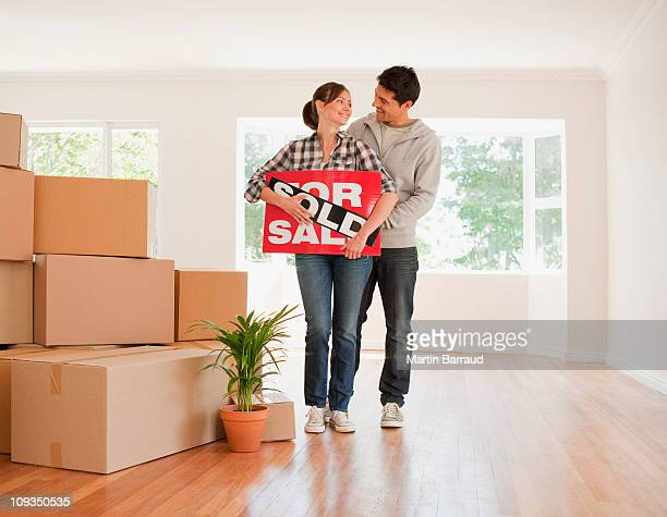 couple holding sold sign for their new house - vendor stock pictures, royalty-free photos & images