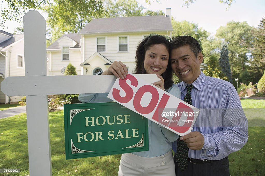 Couple holding sold sign of house : Stockfoto