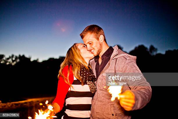 Couple holding sparkles and kissing in park