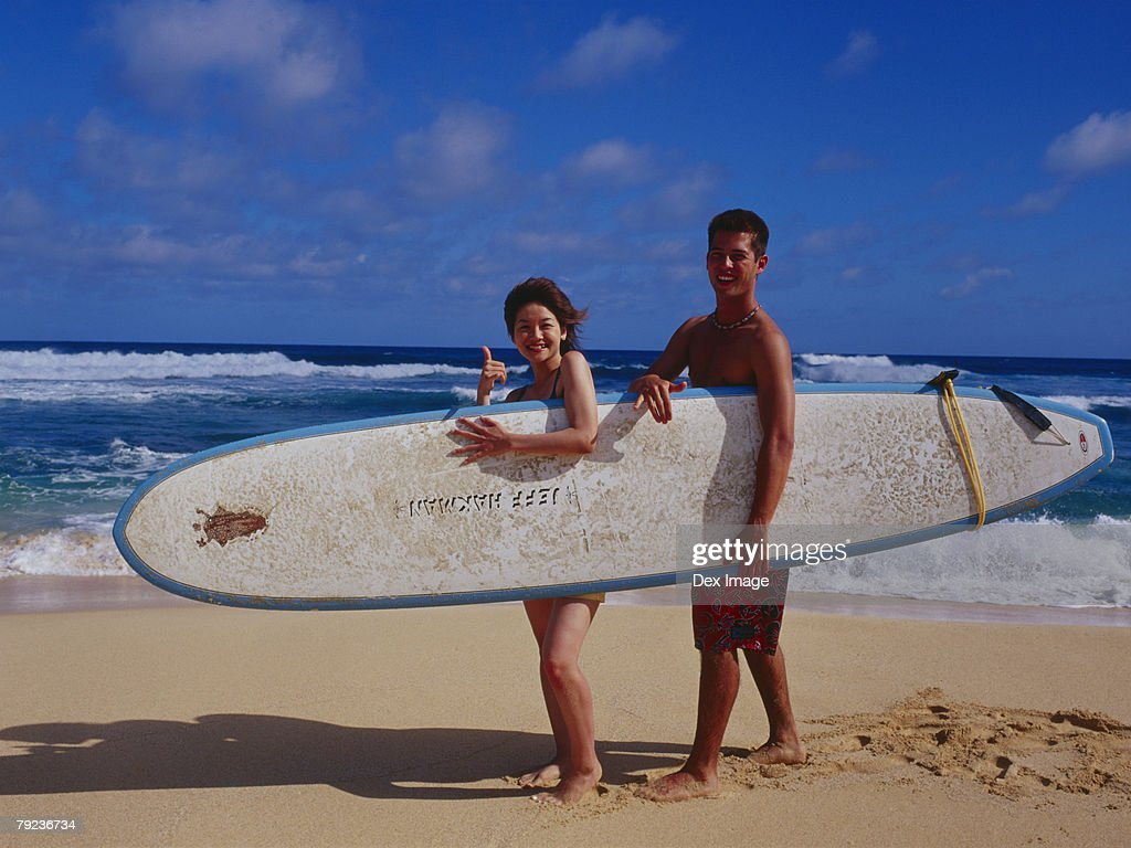 Couple holding surfboard : Stock Photo