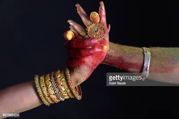 Couple holding their hand while celebrating Holi with colors.