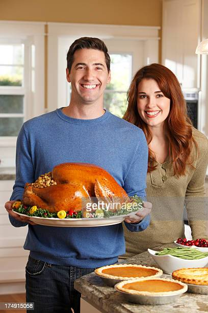Couple Holding Turkey On Platter For Thanksgiving Dinner