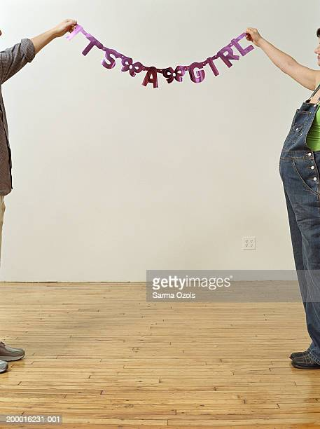 Couple holding up 'It's a girl' sign in apartment