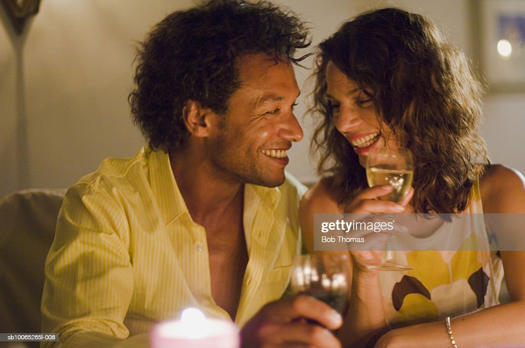 Couple holding wine glass, looking and smiling : Foto stock