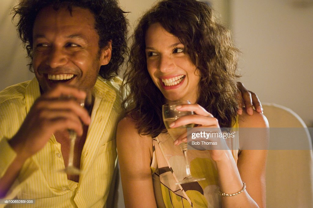 Couple holding wine glass, looking away, laughing : Foto stock