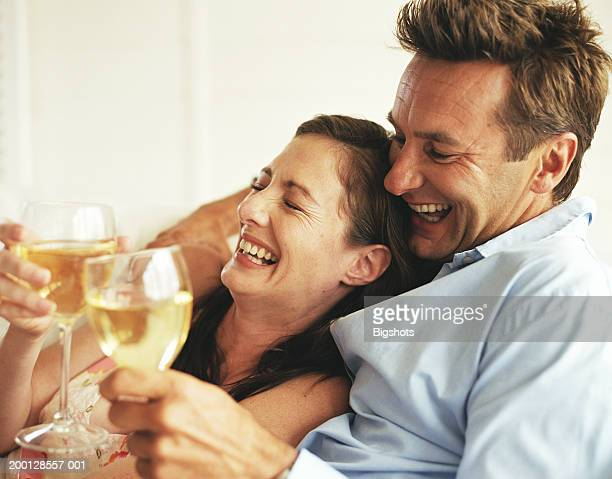 Couple holding wine glasses, laughing, woman leaning on man