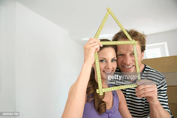 Couple holding yardstick shape house new