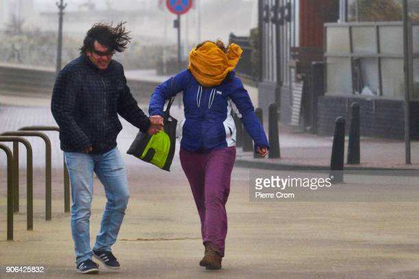 A couple holds hands as a hurricaneforce storm blows galewinds of up to force 12 in The Hague on January 18 2018 in The Hague Netherlands The Dutch...
