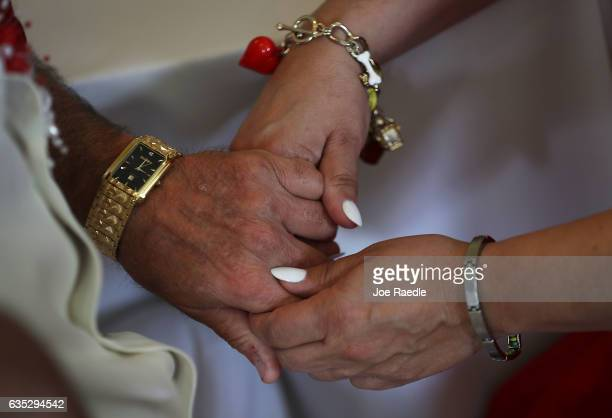 A couple holds hands as they participate in a group Valentine's day wedding ceremony at the National Croquet Center on February 14 2017 in West Palm...