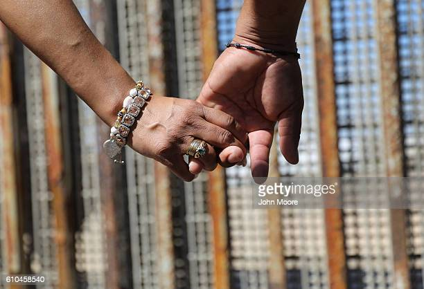 A couple holds hands while meeting loved ones through the USMexico border fence on September 25 2016 in Tijuana Mexico The US Border Patrol opens the...