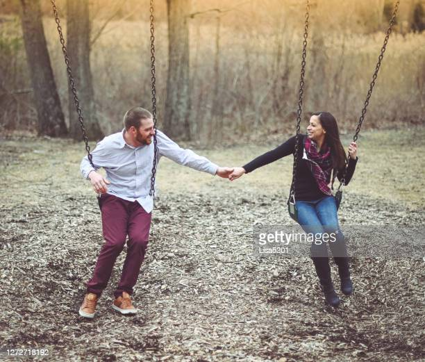 couple holds hands while on swings - offbeat stock pictures, royalty-free photos & images