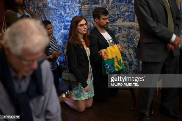 Couple holds the Brazilian imperial flag as they attend a mass at the Gloria old imperial church during the annual gathering of descendants of the...