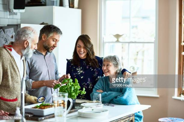 couple hosting their parents and in laws for dinner in family home - two generation family stock pictures, royalty-free photos & images