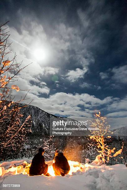 Couple huddling by fire in the snow of the Norwegian wilderness, Myrkdalen, Voss, Norway