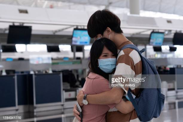 Couple hug at Hong Kong's International Airport on July 18 the day before a deadline by the British government to allow Hong Kongers the right to...