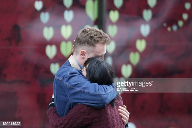 A couple hug at the police corden at the north end of London Bridge in London on June 4 after leaving a bunch of flowers in tribute to the victims of...