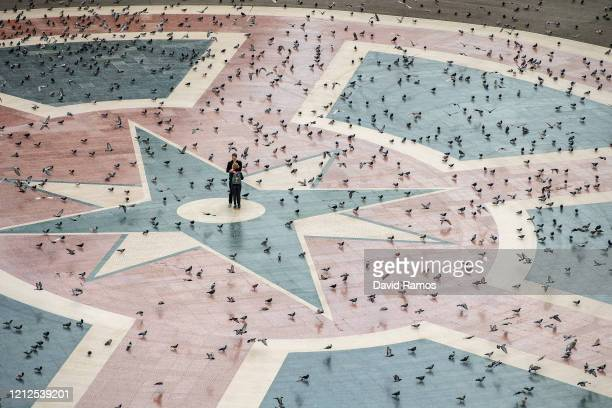 A couple hug each other in an empty Catalunya square on March 15 2020 in Barcelona Spain As part of the measures against the virus expansion the...