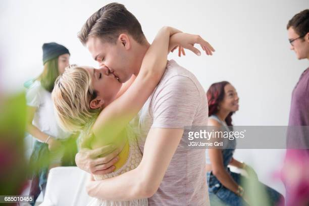 couple hugging and kissing at party - kissing stock pictures, royalty-free photos & images