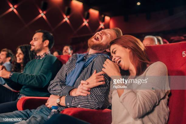 couple hugging and laughing at cinema - comedy film stock photos and pictures
