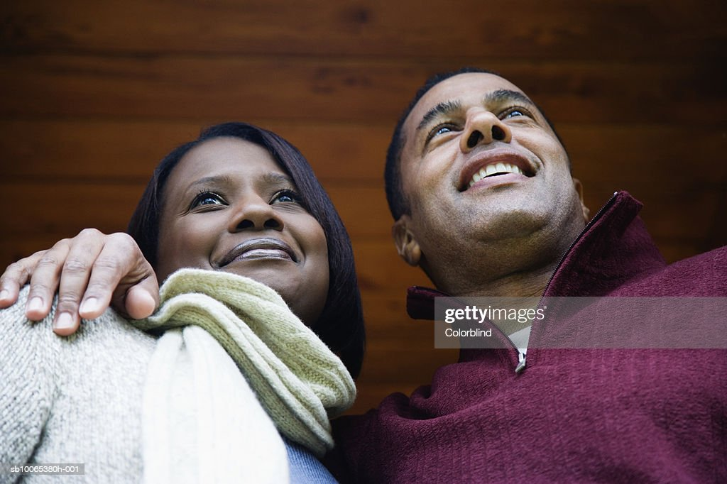 Couple hugging and smiling, low angle view : Foto stock