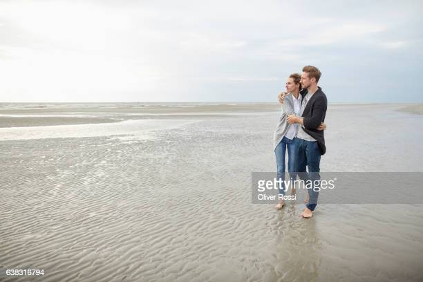 Couple hugging and walking on the beach