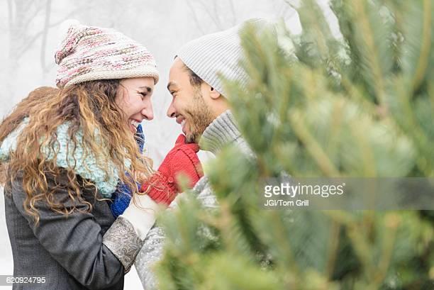 Couple hugging at Christmas tree farm