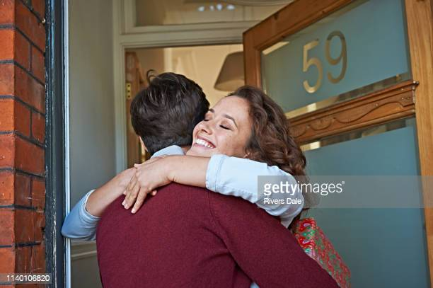 couple hugging at front door - maroon stock pictures, royalty-free photos & images