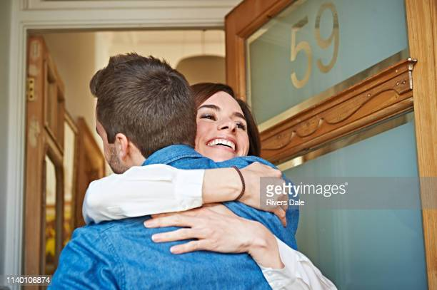couple hugging at front door - greeting stock pictures, royalty-free photos & images