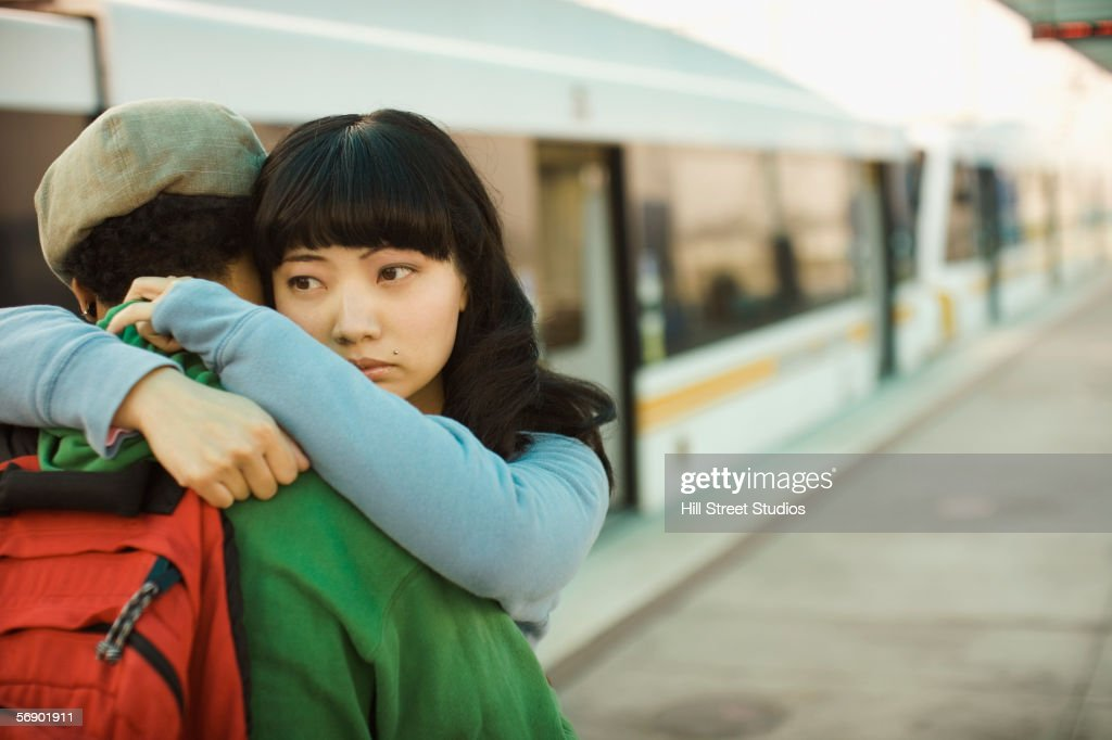 Couple hugging at train station : ストックフォト