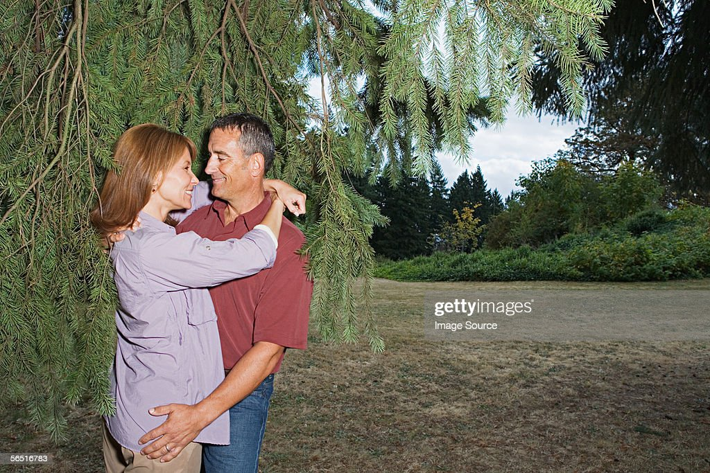 Couple hugging by a tree : Stock Photo