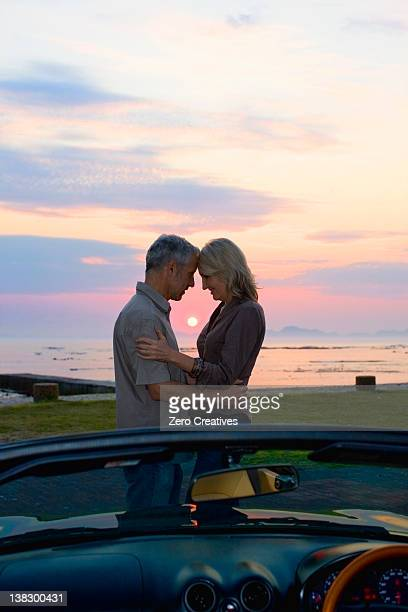 couple hugging by convertible at sunset - three quarter length stock pictures, royalty-free photos & images