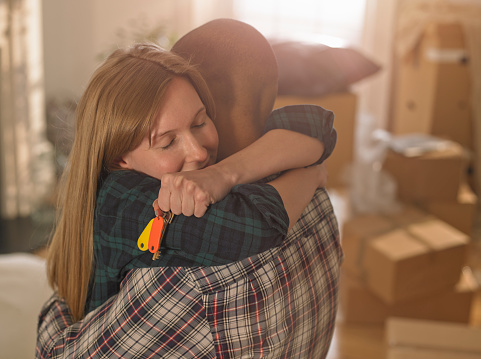 A couple hugging emotionally in their new home - gettyimageskorea
