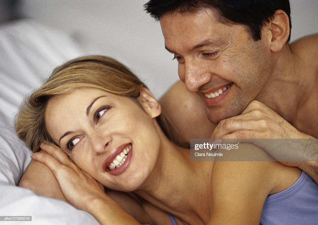 Couple hugging in bed, smiling, close-up : Stockfoto