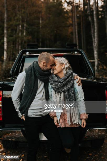 couple hugging in front of car - västra götaland county stock pictures, royalty-free photos & images