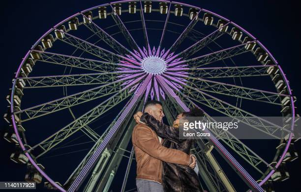 couple hugging in front of ferris wheel at fairground - african american ethnicity stock pictures, royalty-free photos & images