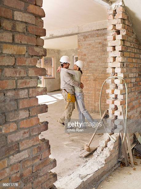 Couple hugging in house under construction