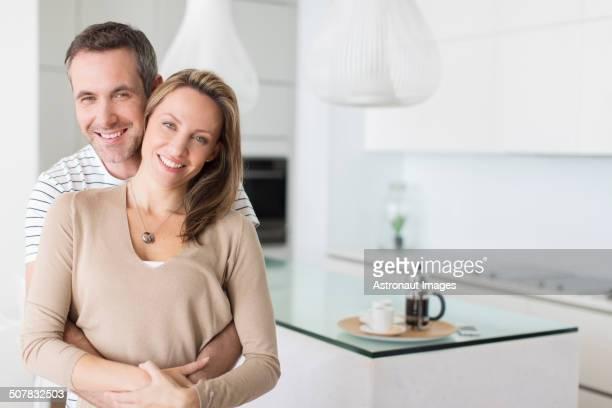 Couple hugging in modern kitchen