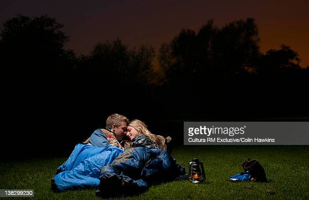 couple hugging in sleeping bags outdoors - newpremiumuk stock pictures, royalty-free photos & images