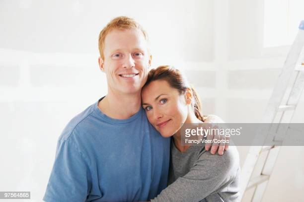 Couple hugging in unfinished home