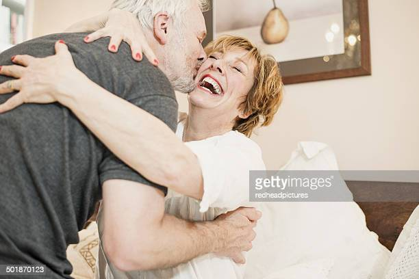 Couple hugging, mature woman laughing